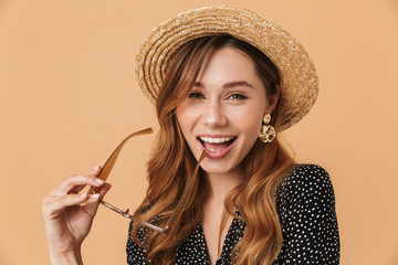 Portrait of adorable woman 20s wearing straw hat smiling and holding sunglasses, isolated over beige background