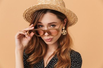 Portrait of modern trendy woman 20s wearing straw hat and sunglasses looking at camera, isolated over beige background
