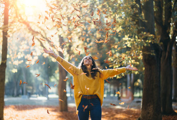 Casual joyful woman having fun throwing leaves in autumn at city park. Wall mural