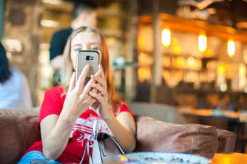 A woman in a cafe at a table does selfie on the phone. A visitor to the restaurant takes pictures of himself on the phone. Woman in red T-shirt and red lipstick