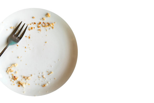 Empty plate with crumbs after eating on a white background. The concept of the end of the holiday or celebration. Nearby place for text