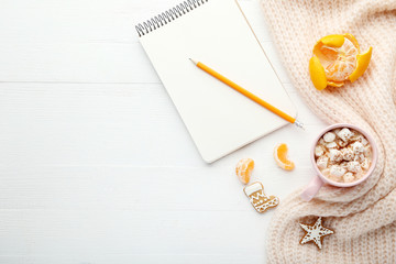 Cup of coffee with notebook, mandarins and gingerbread cookies on wooden table