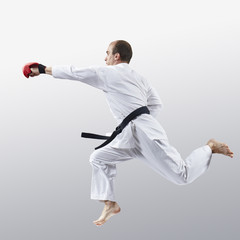 On a light background, an athlete in karategi trains a jab in jump