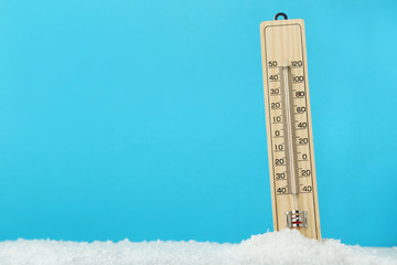 Wooden thermometer in snow on blue background