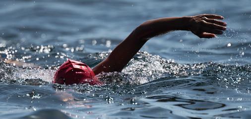 Unknown swimmer at sea, swimming crawl in blue sea,training for triathlon