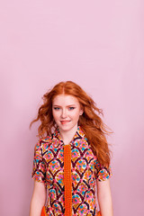 Portrait of beautiful red-haired girl on pink background