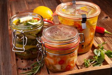 Eingelegte Zucchini und Karotten auf Holzbrett mit geöffnetem Glas