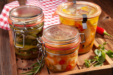 Eingelegte Zucchini und Karotten auf Holzbrett mit kariertem Tuch