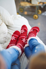 A couple laying on the sofa and wearing red christmas themed socks.