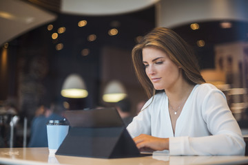 Young businesswoman in a cafe using tablet