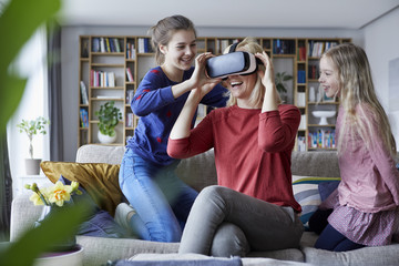 Daughters showing mother how to play with VR glasses