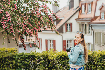 Young beautiful woman enjoying spring in the city, fashion girl wearing denim jacket. Image taken in Lausanne, Switzerland