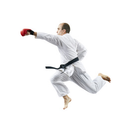 A male athlete trains a punch with his hand in a jump against a white background