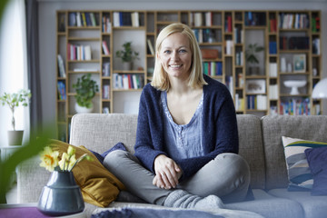 Woman relaxing at home, sitting on couch
