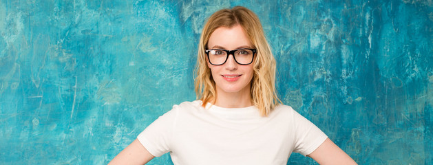 Clever blonde. Close-up portrait of a woman in glasses on a blue background.