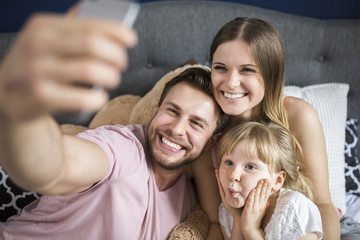 Happy family sitting on bed, taking smartphone selfies