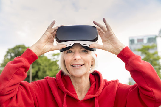 Portrait of smiling senior woman wearing VR glasses