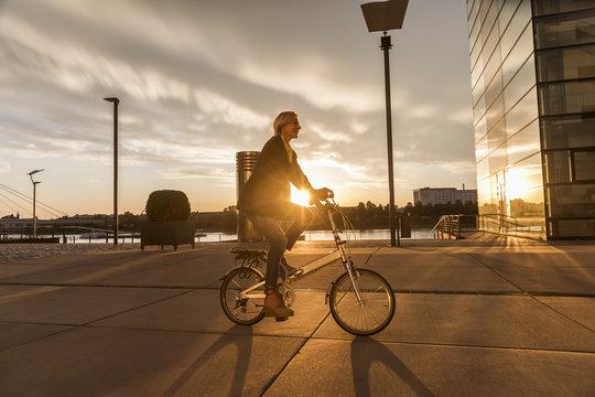 Senior woman riding city bike at the riverside at sunset