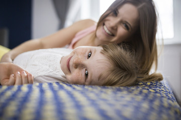 Happy mother and daughter lying on bed