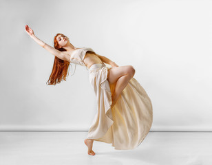 Dancer posing in studio. Young and beautiful redhead girl in a beige long skirt and top dances and poses in studio. Copy space