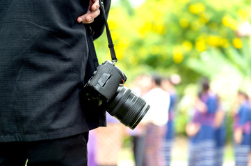 professional photographer concentrate and continue his passion for photography with soft-focus and over light  in the background