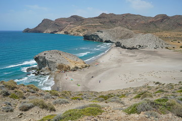 Sandy beach and rock formation on the sea shore, Playa de Mónsul in the Cabo de Gata-Níjar natural park, Mediterranean sea, Almeria, Andalusia, Spain
