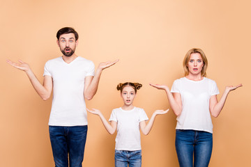 Portrait of young family bieng confused, bearded father, blonde mother and their little daughter wearing jeans and T-shirts, showing uncertain gesture with their hands