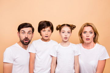 Closeup portrait of young family, bearded father, blonde mother and their little children, boy and girl, wearing white T-shirts showing surprising on camera on beige background