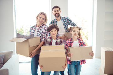 Young happy smiling family four persons wearing casual standing together holding carton boxes with stuff things in light living room moving to new flat