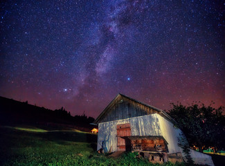 Wall Mural - View at the starry sky and old house on mountain slope.
