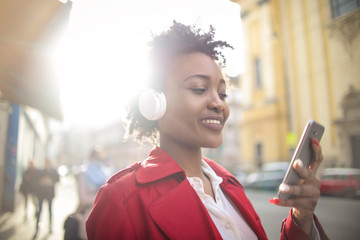 Young woman listening music with headphones while checking her smart phone