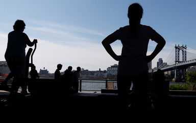 People are seen in silhouette working out during sunny weather in Manhattan, New York