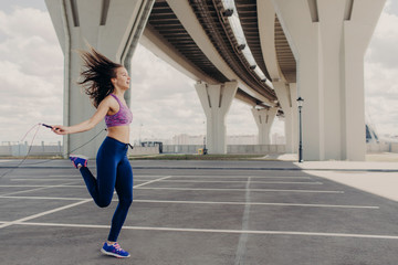 Sideways shot of healthy slim young female with athletic body, jumps with skipping rope, does physical exercises outdoors, wears sportswear. Fitness cardio training with rope. Sport concept.