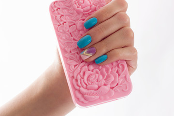 Female hands with blue manicure hold a pink  cover.