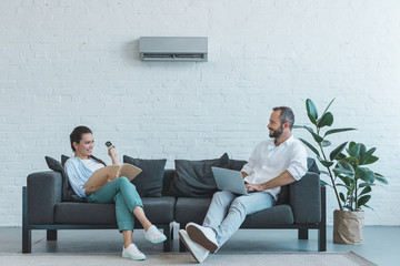 couple turning on air conditioner during the summer heat while sitting on sofa with book and laptop