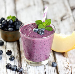 Blueberry smoothies juice a tasty healthy drink in a glass, drink the morning on white wooden background.