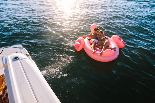 Romantic couple relaxing on inflatable top in sea