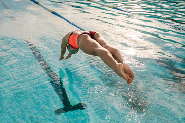 Female swimmer diving into indoor sports swimming pool