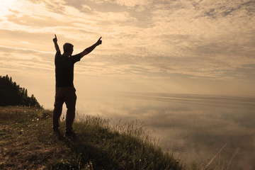 A man stands on top of a mountain and sees the view of nature. The tourist raises his hands and enjoys the fresh air.