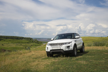Car Land Rover Range Rover is standing at green grass at summer day near the city of Chistopol, Tatarstan, Russia. 8 July 2018. Wall mural