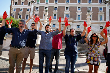 Protesters raise their hands painted red during a protest against the Italian Interior Minister Matteo Salvini in front of the Interior Minister building in Rome