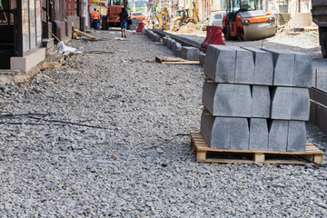 Sidewalk and dug pits filled with gravel and began laying concrete tiles during the reconstruction of the street in the center of the big city
