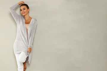 autumn fashion photo of slim young woman and gray wall of free space for your decoration.