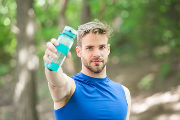 Towards a healthier lifestyle. Athlete drink water after training in park. Man athletic appearance holds bottle with water. Man athlete cares about water balance. Sport and healthy lifestyle