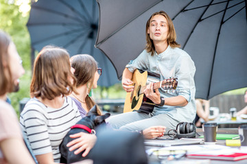 Young friends having fun together playing a guitar sitting at the table outdoors in the park