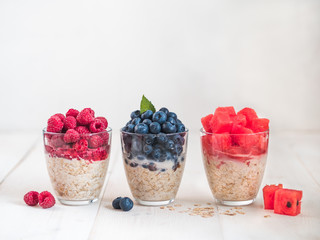 Healthy breakfast: overnight oats with fresh fruits and berries in glass. Overnight oatmeal porridge with watermelon, raspberry, blueberry,decorated mint. Overnight oats on white background,copy space