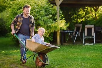 Happy little boy having fun in a wheelbarrow pushing by dad in domestic garden