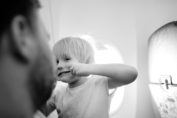 Portrait of crazy and silly little boy with his tired father during traveling by an airplane