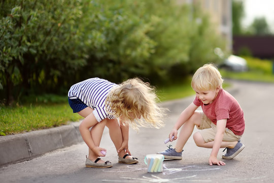 Happy little boy and girl drawing with colored chalk on asphalt