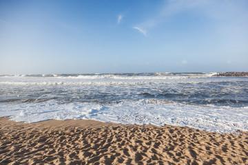Wall Mural - Beautiful sandy ocean coast, waves and blue sky